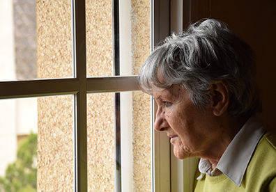 Anziana donna triste guarda dai vetri di una finestra chiusa 11833d12503f